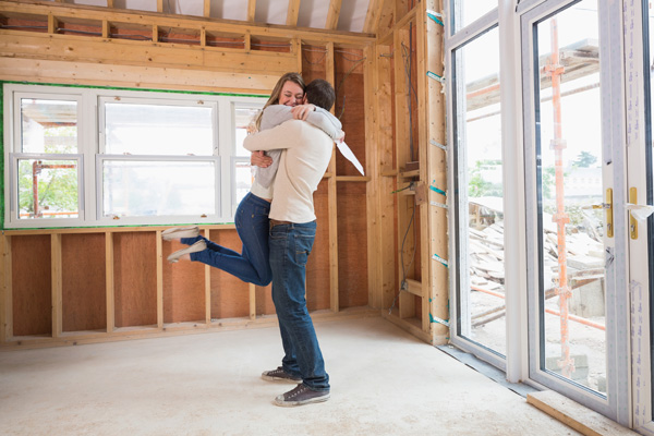 A happy couple hugging within a house that's under construction